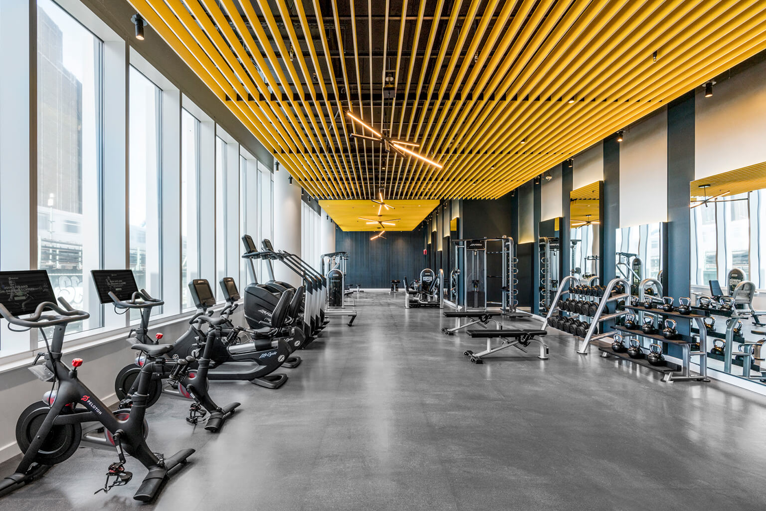 Fitness center with Peloton bikes, Stairmaster machines, kettlebells, and dumbbells