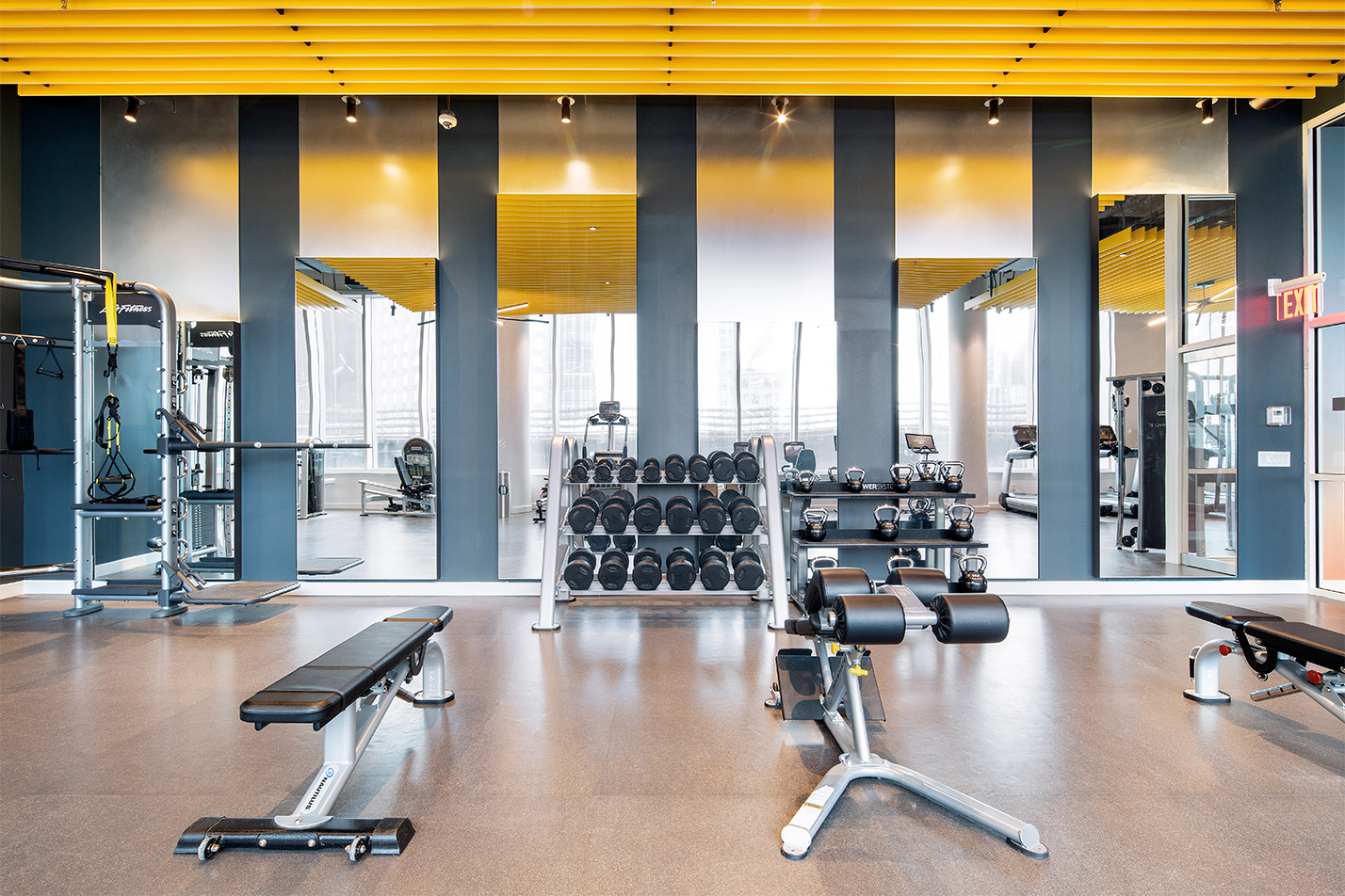 Fitness center with dumbbells, kettlebells, flat bench, and incline bench