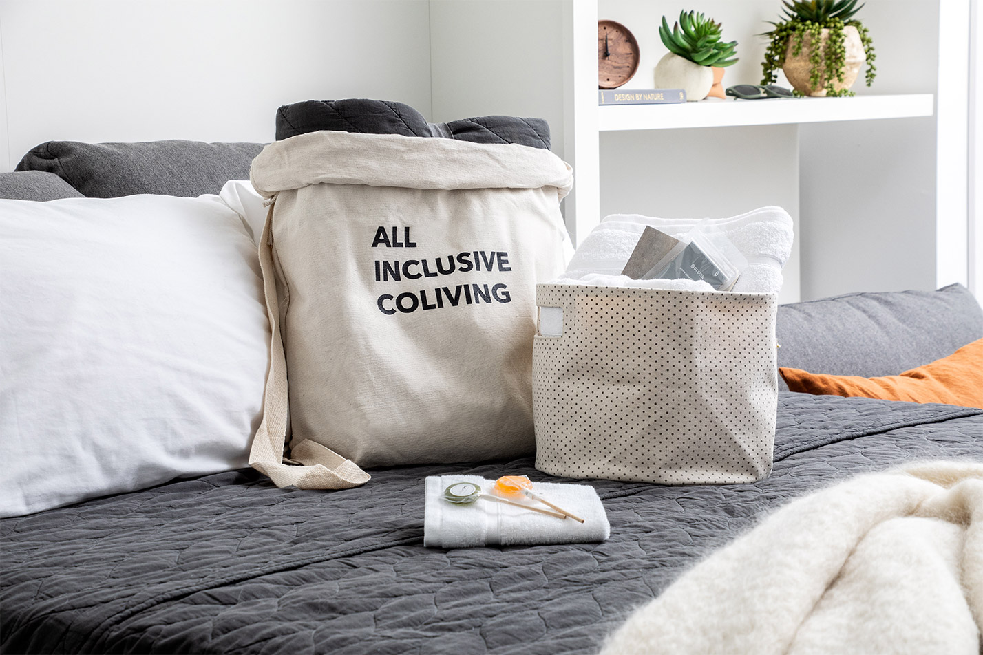 Welcome gift set on bed including towels, lollipops, and 'All inclusive coliving' Ollie tote.