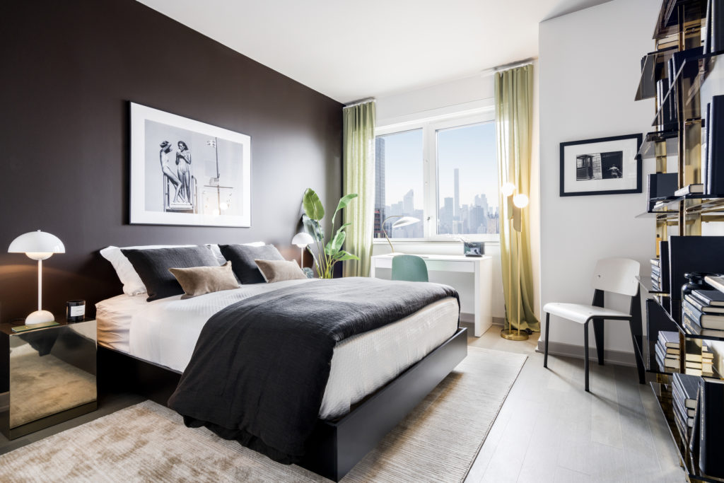 Luxury bedroom with queen-sized bed, side table, desk with chair, and bookcase, overlooking skyline of New York
