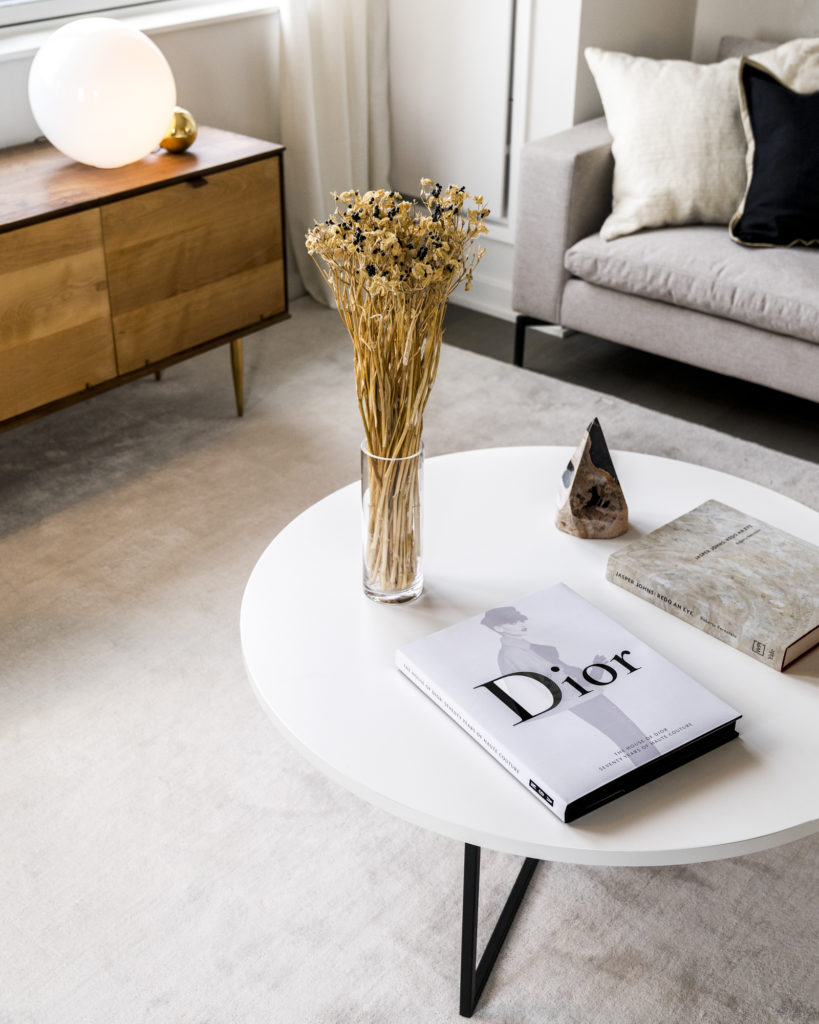 Closeup of white coffee table in Luxury unit, on which sits a variety of books, flowers in a vase, and a stone art piece