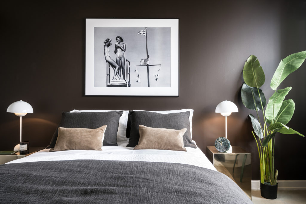 Detail of queen-sized bed in Luxury bedroom, showcasing bedside tables with lamps, picture frame on wall, and plant decoration on floor