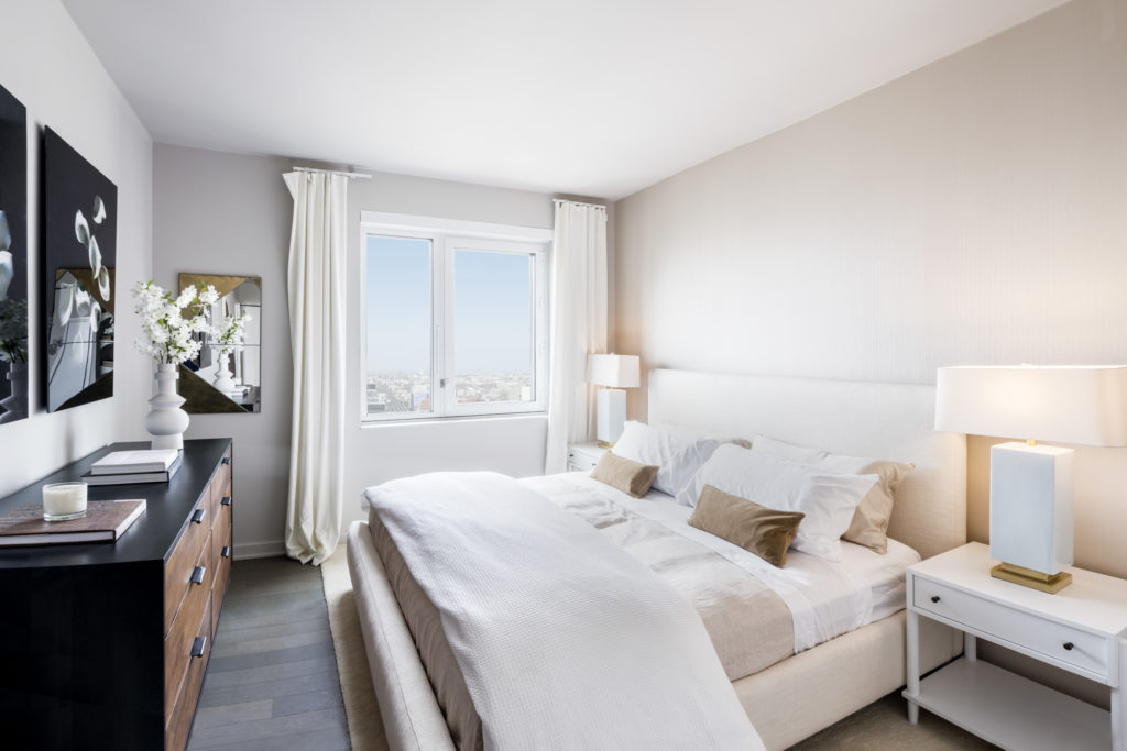 Luxury bedroom with queen-sized bed, side table, and wood dresser, with view overlooking Queens